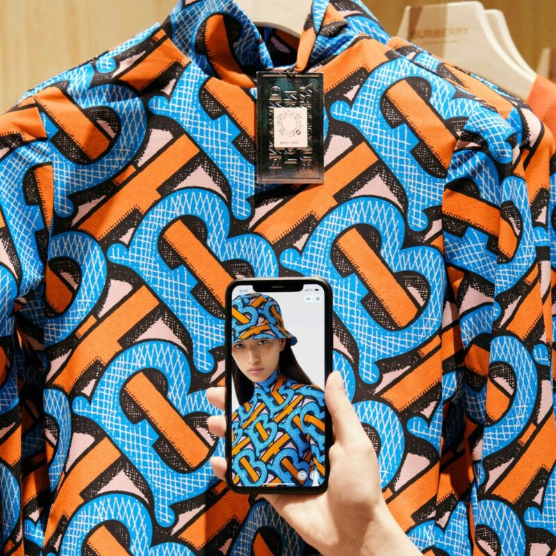 One hand holds a smartphone in front of a piece of clothing