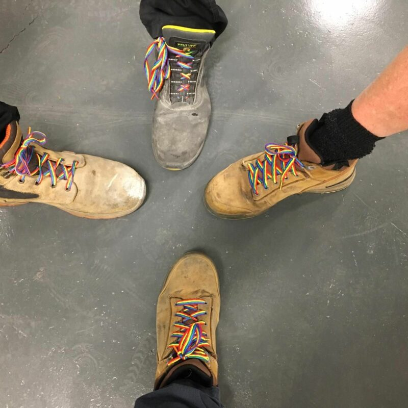Four work boots laced with colorful laces of four people standing in circle