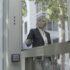 Eine Frau geht in ein Geschäft und hält ein Smartphone an ein Lesegerät