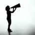 A silhouette of a woman calling into a megaphone