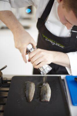 Ein Koch würzt Fische auf einer Platte