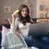 Frau sitzt auf dem Sofa und shoppt online eine Kreditkarte in der Hand haltend